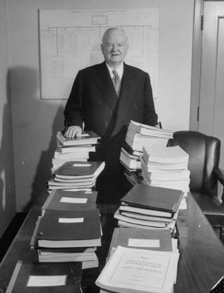 Former President Herbert C. Hoover, in 1949, standing in back of stacks of reports for Hoover Commission Studies.