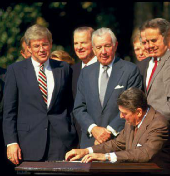 Then-Congressman Kemp watching President Reagan sign the tax reform bill of 1986